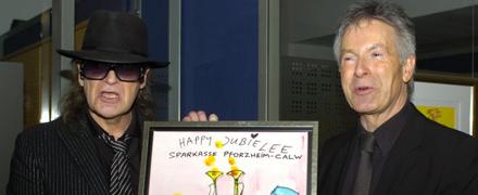 Udo Lindenberg überreicht sein Jubiläumsbild an den Vorstandsvorsitzenden der Sparkasse, Dr. Herbert Müller
